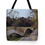 A Hilly Country Road Passes A Fenced Tote Bag