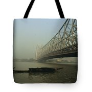 A Man Guides A Boat Under A Bridge Tote Bag