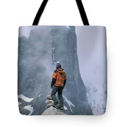 A Man Stands On A Cliff Watching Tote Bag