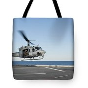 A Sailor Directs A Uh-1n Huey Tote Bag