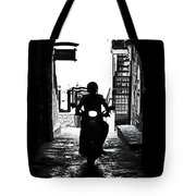 a scooter rider in the back light in a narrow street in Italy Tote Bag by Joana Kruse