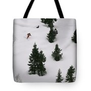 A Skier Makes His Way Down A Hill Tote Bag