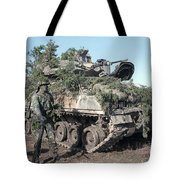 A Soldier Stands Beside A Camouflaged Tote Bag
