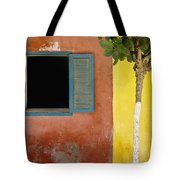 A Tree Outside A Colorful Building And Tote Bag