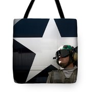 An Airman Stands In Front Of A C-2a Tote Bag