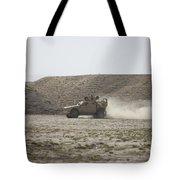 An M-atv Races Across The Wadi Tote Bag