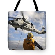 An Sh-60b Sea Hawk Helicopter Releases Tote Bag