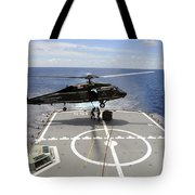 An Sh-60f Sea Hawk Helicopter Lowers Tote Bag