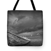 Boat Stranded On A Beach Covered By Menacing Storm Clouds Tote Bag