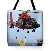 Boatswain Mate Directs A Hh-65a Dolphin Tote Bag by Stocktrek Images