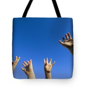 Childrens Hands Reach Toward The Blue Tote Bag