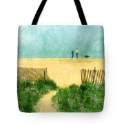 Couple Walking Dog On Beach Tote Bag by Jill Battaglia
