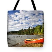 Red Canoe On Lake Shore Tote Bag
