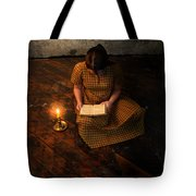 Schoolgirl Sitting On Wood Floor Reading By Candlelight Tote Bag