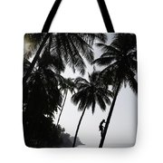 Silhouetted Man Climbing A Palm Tree To Tote Bag