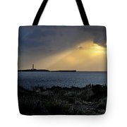 storm light - A morning light iluminates lighthouse through clouds in an amazing landscape Tote Bag