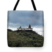 The Structure Of An Abandoned Temple On The Top Of A Green Covered Hill With Blue And White Clouds I Tote Bag