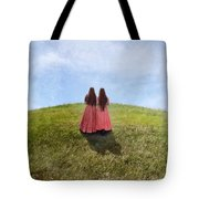 Two Girls In Vintage Dresses Walking Up Grassy Hill Tote Bag
