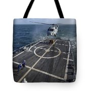 U.s. Navy Sailors Prepare To Attach Tote Bag