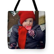 Baby In Red Hat Sits On A Bench In The Street With Candy Tote Bag