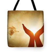 Raised Hands Catching Sun On Sunset Sky. Concept Of Spirituality, Wellbeing, Positive Energy Tote Bag