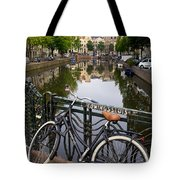 Bicycle Parked At The Bridge In Amsterdam. Netherlands. Europe Tote Bag