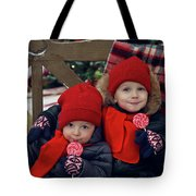 Two Children Sitting On A Bench With Candy Tote Bag