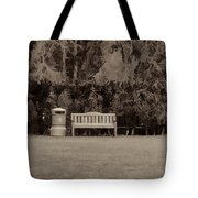 A Trash Can And Wooden Benches In A Small Grassy Area Tote Bag
