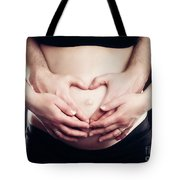 A Couple Touching Belly In A Heart Shape. Tote Bag