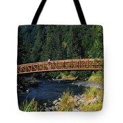 A Hiker Crosses A Bridge Tote Bag