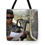 A Honduran Crew Chief Consults Tote Bag