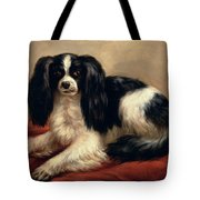 A King Charles Spaniel Seated On A Red Cushion Tote Bag