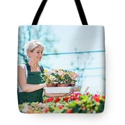 Attractive Gardener Selecting Flowers In A Gardening Center. Tote Bag