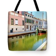 boat in a canal of the colorful italian village of Comacchio in  Tote Bag