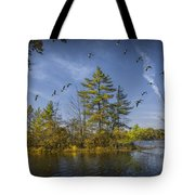 Canada Geese Flying By A Small Island On Hall Lake Tote Bag