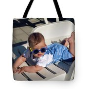 Child In A Denim Suit And Sunglasses Lying Tote Bag
