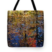Colorful Leaves Floating In A Still Pond Reflecting Trees In The Tote Bag