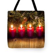 Glowing Red Candles With Snow Covered Evergreen Branch On Rustic Tote Bag