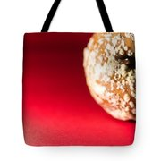 Old Rotting Apple With Fruit-rot On Red Background Tote Bag