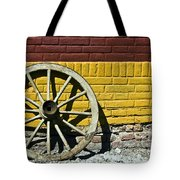 Old Wooden Wheel Against A Wall Tote Bag