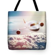 Passenger Airplane Flying At Sunset, Blue Sky. Tote Bag