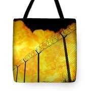 Realistic Orange Fire Explosion Behind Restricted Area Barbed Wire Fence, Blurred Background Tote Bag