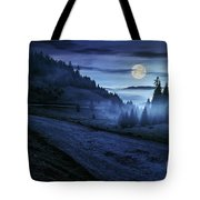 Road Near Foggy Forest In Mountains At Night Tote Bag