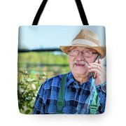 Senior Gardener Talking On The Phone With A Client. Tote Bag