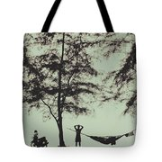 Silhouette Of A Young Men With Crossed Hands Above His Head Camping Hammocking In The Nature Tote Bag