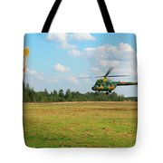The Helicopter Over A Green Airfield. Tote Bag