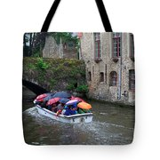 Tourists With Umbrellas In A Sightseeing Boat On The Canal In Bruges Tote Bag