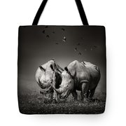 Two Rhinoceros With Birds In Bw Tote Bag