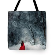 Woman In Red Cape Walking In Snowy Woods Tote Bag