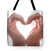 Woman's Hands Make A Heart Shape On White Background, Backlight. Love Tote Bag